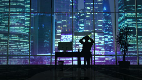 Silhouette of a man working late in the office at the computer Animation