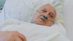 Senior woman in hospital bed Live Action