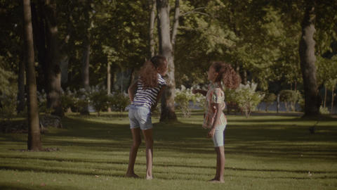 Two smiling little sisters giving high five outdoors Footage