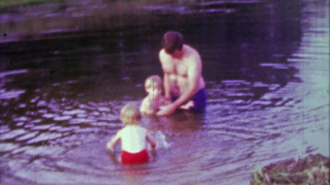 1967: Fun hairy soft dad playing with kids in dirty pond water Footage