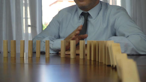 Wooden blocks falling in line domino effect business concept Live Action