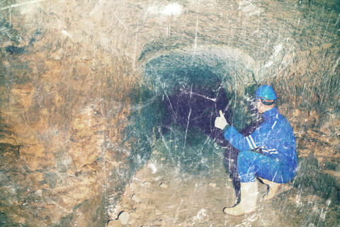 Man worker check something in abandoned mine tunnel フォト