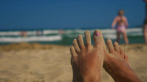 Lazy feet on the beach with sand on toes Live Action