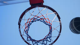 Basketball bumping into hoop and passing through ring, outdoor gym with blue sky Footage