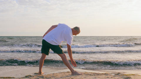 Adult man practising yoga pose on sea beach. Yoga training on empty beach Footage
