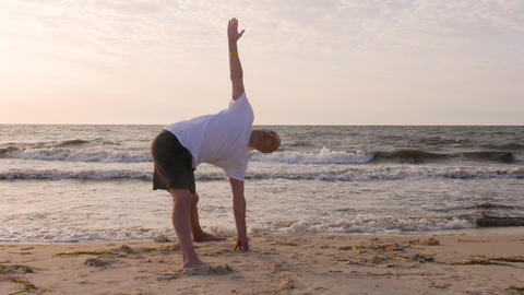 Man standing in yoga pose while morning training on sea beach Footage