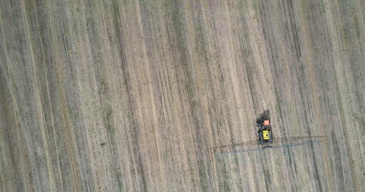 flight over tractor sprayer with long bars moving on field Live Action