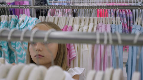 Teenager girl choosing clothing in fashion store. Fashion and shopping concept Live Action