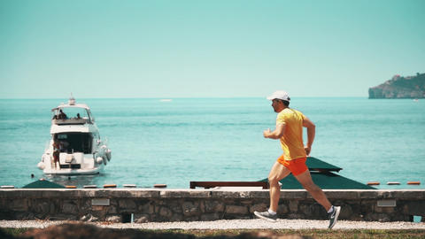 Slow motion shot of an athletic man running at seaside Footage