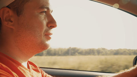 Confident man driving a car on sunny summer day, close-up Live Action
