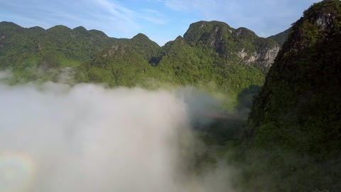 green forestry mountains above fog against blue sky Footage
