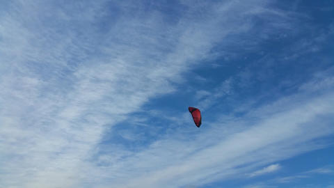 Red paraglider on a background of blue sky with clouds. No sound Footage