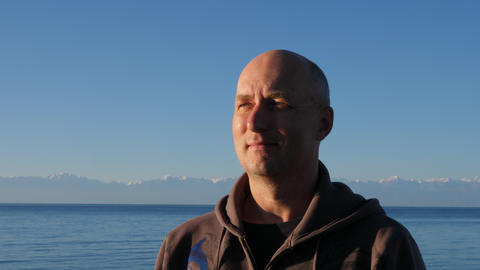 Portrait adult man on mountain peaks and blue lake Issyk Kul landscape Footage