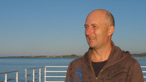 Portrait handsome man on blue sea looking away on blue sea background Footage