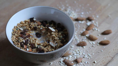 Pouring milk in a bowl with granola Stock Video Footage