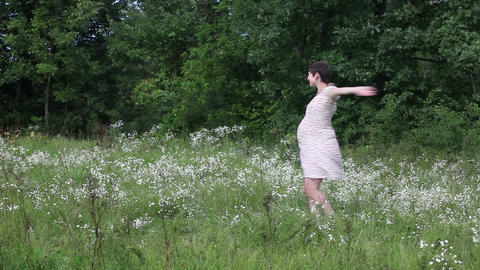 Pregnant woman dancing in the field Footage