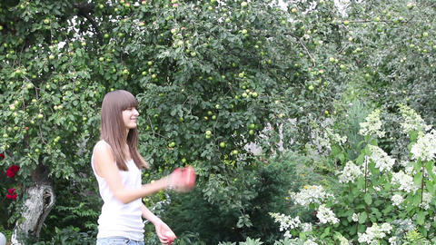 Pretty girl juggling with three apples Stock Video Footage