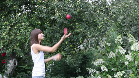 Pretty girl juggling with three apples Footage