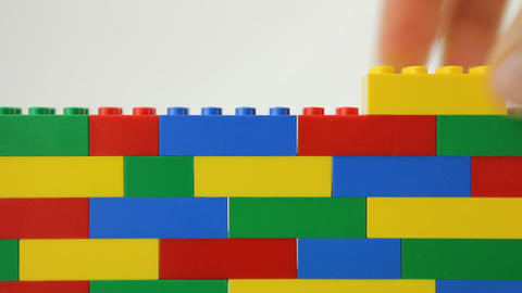 Hand adding block to lego wall Footage