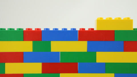 Hand adding block to lego wall Stock Video Footage