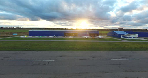 Small Airplanes Near Hangar At Sunset Footage