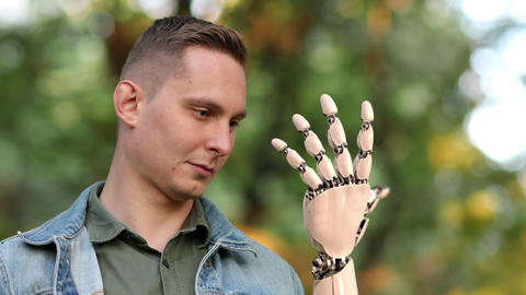 Young Man Looks on His Robotic Hand ビデオ