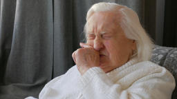 Old woman is rubbing nose Live Action