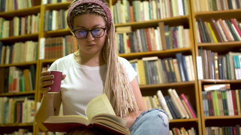 Beautiful girl reading a book in the library Live Action