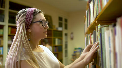 Beautiful girl chooses a book in the library Live Action