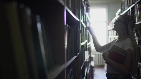 Beautiful young girl between the rows with books in the library Live Action