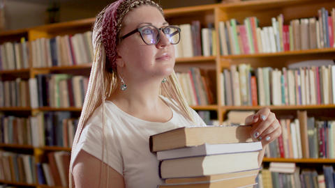 Beautiful girl with books in the library Footage