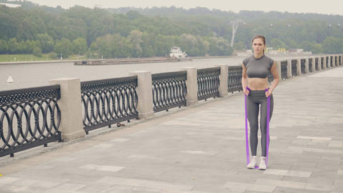 Fitness woman using sport expander for workout training outdoor. Active Footage