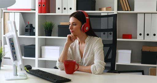 businesswoman listening music, looking to monitor and waving hand at camera Footage