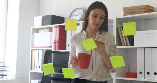 businesswoman standing near glass wall with sticky notes and using smartphone Live Action