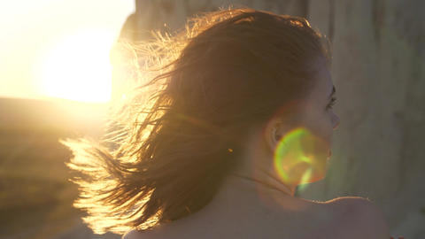 Shoulders of young woman and sun rays thru her hair Live Action
