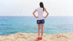 Woman stand at edge of cliff on sunny day in slow motion. Carefree female look ビデオ
