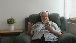 Old woman is listening music (old hits) on a smartphone Live Action