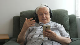 Old woman is listening folk music on a smartphone. Closeup shot Live Action