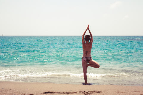 Young woman practicing yoga on the shore of the sea フォト