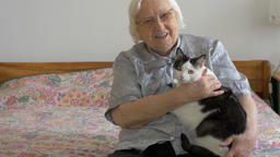Senior woman is talking to a cat. Portrait of an old woman with a cat Footage