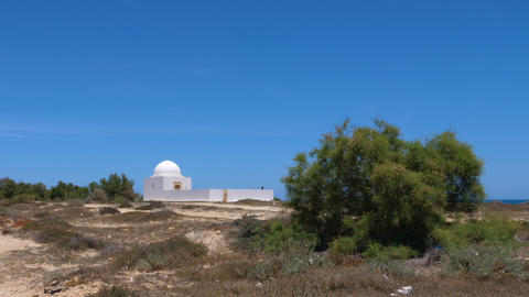 Lonely white stone chapel at sea island on blue sky background Footage