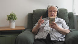 Old woman is listening folk music on a smartphone Live Action