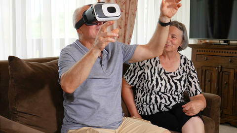 Positive senior couple trying up virtual reality glasses 영상물