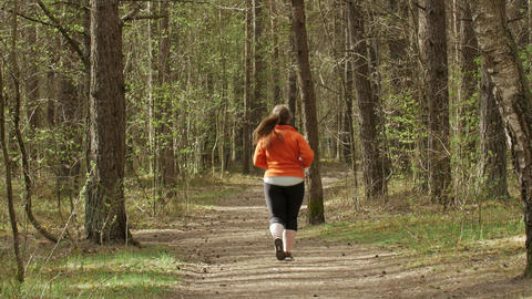 Back view of an unrecognizable woman running in the forest GIF
