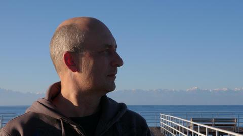 Portrait caucasian man on mountain landscape and lake Issyk Kul close up Footage