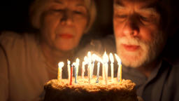 Loving senior couple celebrating anniversary with cake at home in the evening Footage