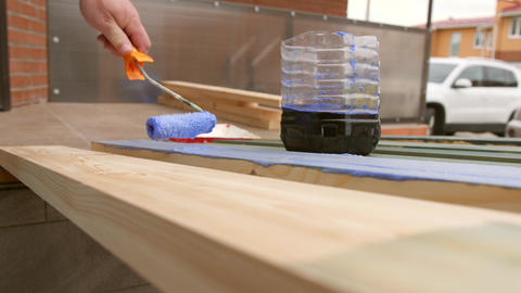 Carpenter Painting a Terrace Wooden Board with Impregnation Water Proofing or Footage