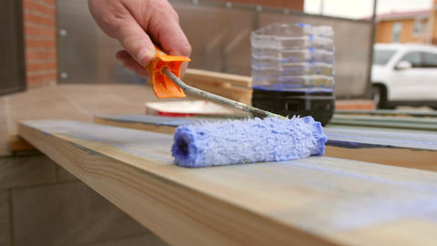Man Painting a Terrace Wooden Board with Impregnation Water Proofing or Paint Live Action
