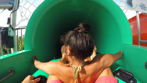 Young Mixed Race Couple Having Fun Riding Down in a Water Slide Tube. 4K Extreme Live Action