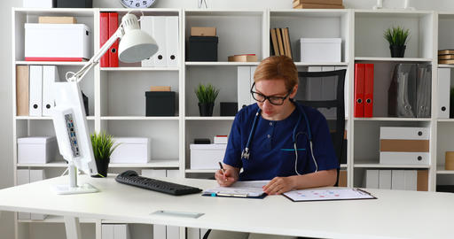 doctor in blue lab coat sitting at workplace and marking documents Footage